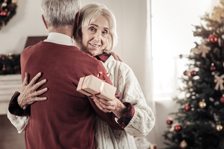 Warm hugs. Attractive elderly female smiling while holding present and looking at camera Stock Photo