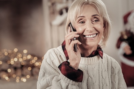 Waiting for you. Elderly female person expressing positivity and holding telephone near right ear while looking aside
