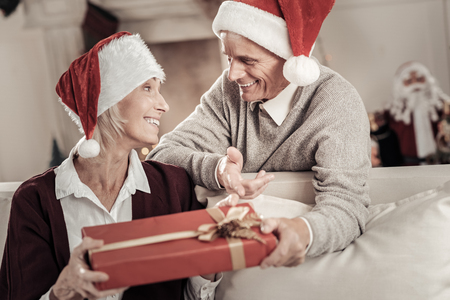 Being surprised. Delighted man expressing positivity while talking with his wife and wearing Christmas hat Stock Photo