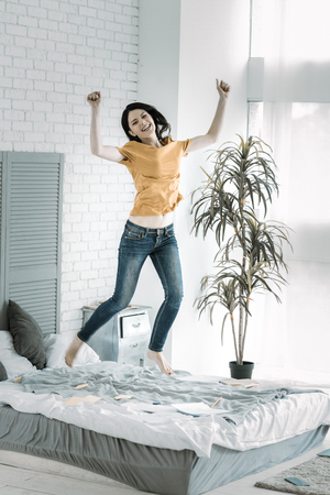 With flying colors. Merry exuberant female student jumping on bed while shouting and rising hands Stock Photo