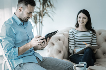 Advanced tablet. Appealing charming successful man siting on chair while smirking and carrying tablet