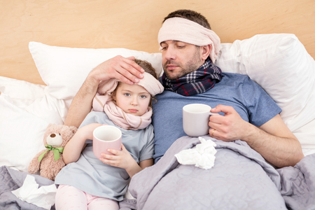 Hot tea. Miserable ill girl and daddy lying in bed and drinking hot tea