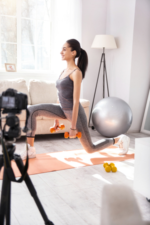 Supple figure. Cheerful slender woman recording herself on camera while doing lunges and holding dumbbells Stock Photo