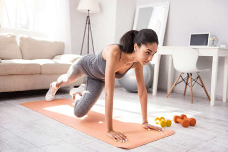 Advanced exercise. Charming dark-haired woman doing a plank and alternating her legs while exercising in the morning