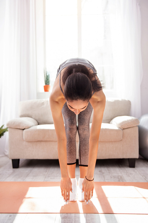 Perfectly supple. Athletic young woman bending forward and touching the floor while working out in the morning at home