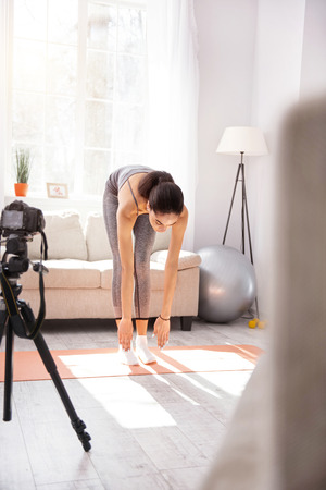 Testing suppleness. Athletic dark-haired woman trying to touch her toes during a workout session at home while filming herself on camera
