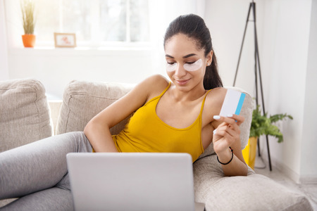 Fast and convenient. Upbeat young woman comfortably lying on the sofa and making an online payment for a purchase with her credit card Stock Photo