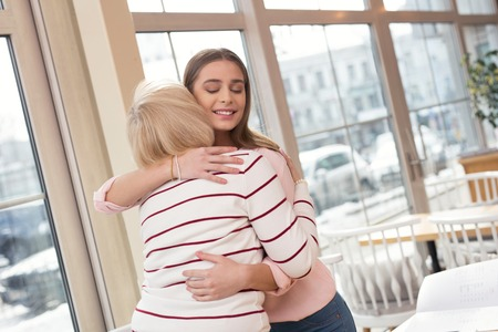 Family ties. Pretty cheerful granddaughter meeting with her granny and hugging her Stock Photo