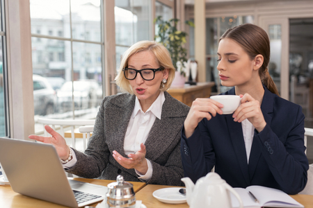 Best partners. Concentrated young woman talking about business with her partner while having tea
