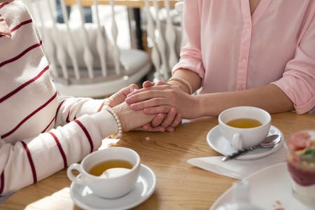 Beste oma. Liefdevolle zorgzame kleindochter hand in hand met haar oma terwijl ze thee drinkt Stockfoto