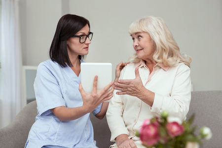Modern gadget. Pleasant elder woman learning to use tablet while nurse touching her shoulder
