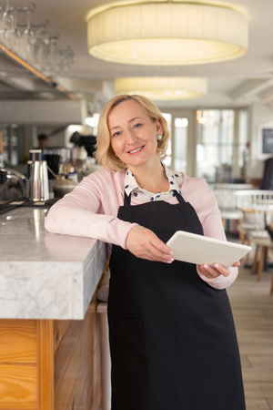 My working hours. Exuberant aged waitress holding a tablet and smiling
