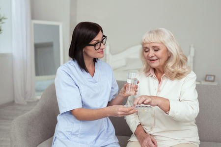Time for medication. Attractive caregiver holding container for drugs while elder woman taking pills
