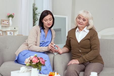 Danger from diabetes. Nurse using blood glucose meter while sad elder woman sitting on sofa