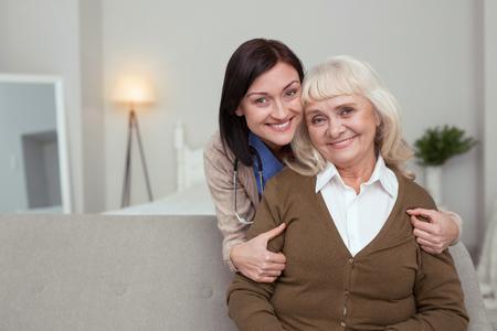 Strong bond. Joyful nurse embracing elder woman who smiling to camera Stock Photo