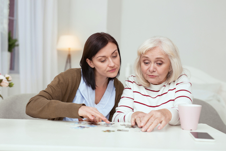 Pleasant time spending. Jolly elder woman and caregiver sitting while gathering puzzle Stock Photo