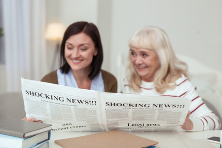 Funny story. Cheerful elder woman and caregiver reading news and chatting Stock Photo