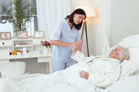 Be strong. Hopeful charming nurse touching elder woman hand who resting in bed Stok Fotoğraf