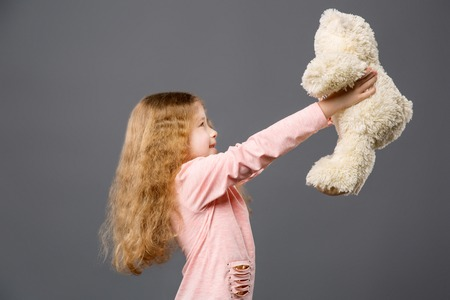 Pleasant cheerful girl looking at her bear while holding it in front of her