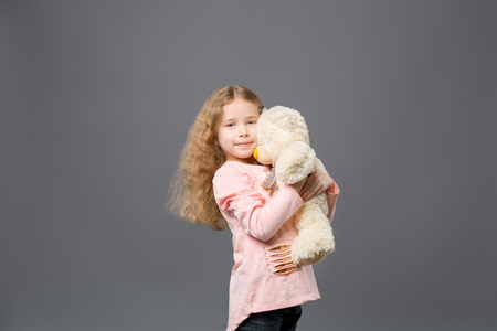 Delighted nice girl standing with her toy while looking at you Stock Photo