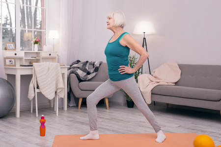 Supple muscles. Charming slim senior woman stretching herself in the morning, doing lunges on yoga mat in the living room Stock Photo