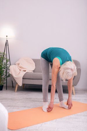 Flexible muscles. Grey-haired senior woman doing bending exercise and touching her toes while stretching in the morning Stock Photo