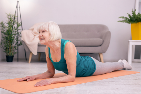 Healthy spine. Upbeat young woman lying on the yoga mat and lifting her torso up, stretching the muscles of her neck and keeping the head straight