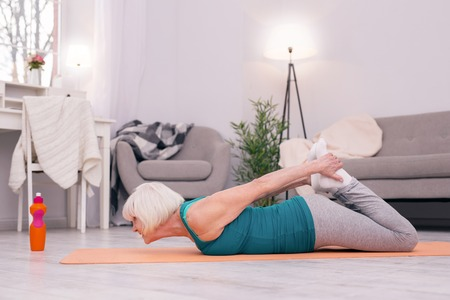 Stretching back. Athletic elderly lady lying on the yoga mat and grabbing her feet while trying to do a king cobra pose