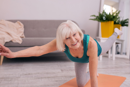 Fun while exercising. Cheerful elderly woman smiling at the camera while standing on one knee and doing a stretching exercise in the morning Stock Photo