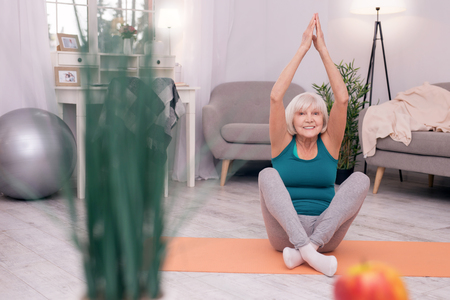Relaxing while exercising. Upbeat senior woman sitting on the mat and practicing yoga while smiling pleasantly Stock Photo