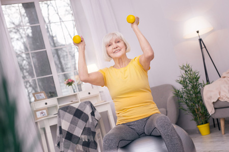 Great mood. Upbeat senior woman sitting on the yoga ball and exercising with dumbbells while smiling happily Stock Photo