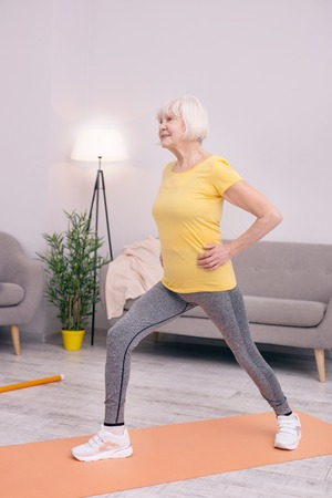 Dynamic exercises. Charming elderly lady doing lunges at home while carrying out morning calisthenics