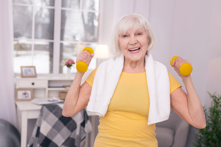 Generating endorphins. Beautiful senior woman lifting up dumbbells and laughing happily while exercising in the morning