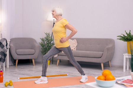 Enjoy dynamic exercises. Slim elderly woman doing morning calisthenics in the living room and performing lunges Stock Photo