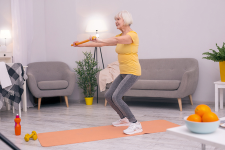 Living healthy life. Athletic elderly woman doing squats in her living room while holding a health wand for correct posture Фото со стока