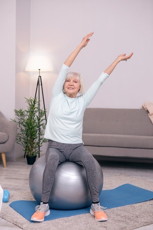 Positive mood. Upbeat elderly woman sitting on the balance ball and leaning to the side while stretching herself