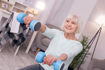 Enjoying workout. Pleasant senior woman grinning while sitting on the floor of the living room and holding a pair of blue dumbbells