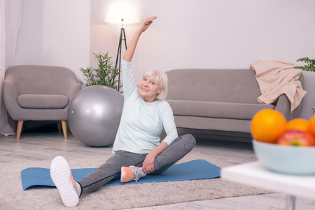 Pleasant warm-up. Beautiful senior woman sitting on the yoga mat and smiling at the camera while stretching herself before a workout