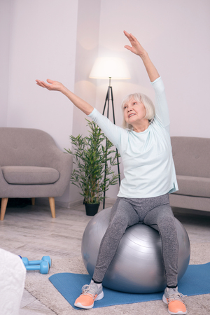 Nice for health. Pleasant elderly woman leaning sideways while sitting on the yoga ball and doing a stretching exercise