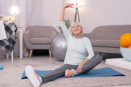 Having fun. Upbeat elderly woman sitting on the yoga mat and pulling one of her legs closer to the pelvis while smiling happily at the camera