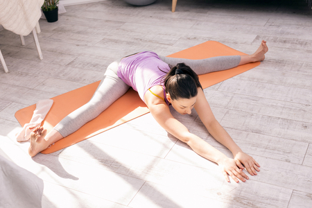 I love training. Slim concentrated woman sitting on the carpet and doing some exercises Stok Fotoğraf