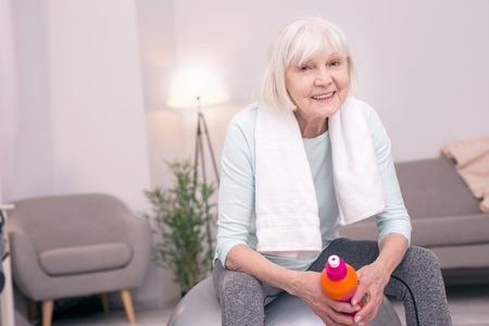 Well-deserved rest. Pleasant upbeat senior woman sitting on the yoga ball and smiling at the camera while having rest after exercising