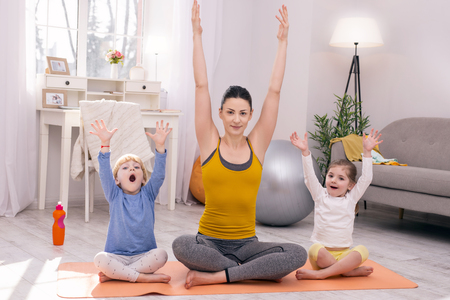 My happiness. Content dark-haired mother and her children sitting on the carpet and doing yoga