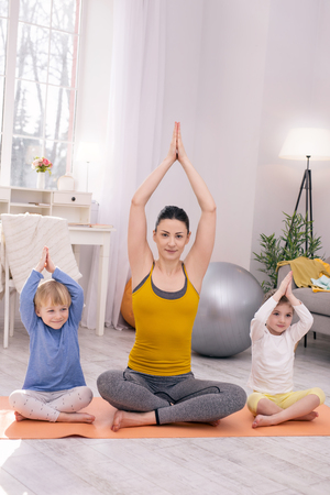 Inspiration. Smiling dark-haired mother and her children sitting on the carpet and doing yoga Stock fotó