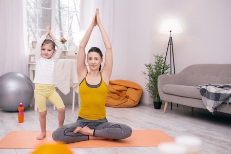 Happy family. Exuberant well-built mother doing some exercises with her daughter while standing on the carpet