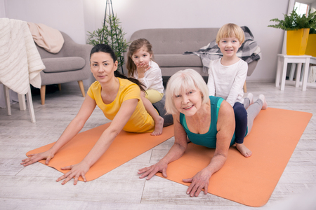 I love sports. Alert aged woman sitting on the carpet and exercising with her daughter and grandchildren