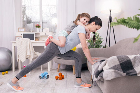 In high spirits. Determined athletic mother training at home and holding her daughter on her back