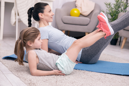 We love sports. Inspired active mother and daughter training their legs while sitting on the carpet