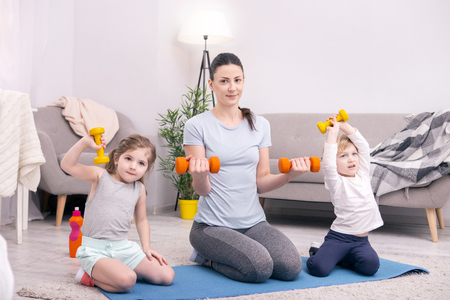 Personal trainer. Exuberant young mother and kids smiling and training with hand weights