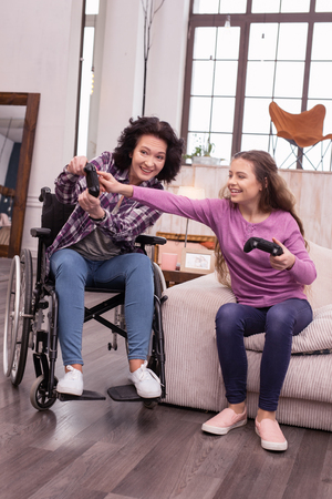 Push this. Happy incapacitated woman and girl using controller while sitting